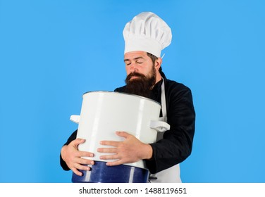 Male chef cook holds big pot. Cooking, culinary. Food, profession and people concept. Cook man in apron holds saucepan in kitchen. Cooking pot, saucepan, casserole. Cookware, dinnerware, kitchenware.