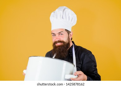 Male chef cook holds saucepan. Cookware, tool, kitchenware. Professional cookery concept. Cook preparing food in restaurant kitchen. Chef cooking food in saucepan. Chief chef with saucepan in kitchen.