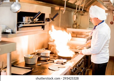 Male chef cooking in a frying pan on a kitchen