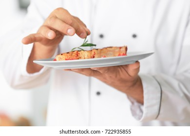 Male chef cooking meat in kitchen, closeup