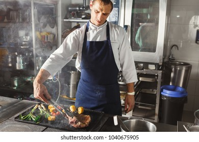 Male chef cooking medium beef steak and vegetables on grill. Healthy exclusive food prepared at professional kithen, closeup