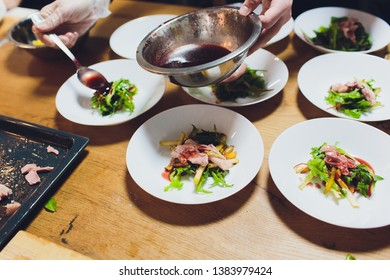 A male chef decorates a salad dish in a restaurant kitchen in a black apron. closeup of a hand with tongs.