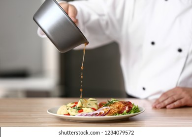Male chef dressing tasty dish in kitchen, closeup