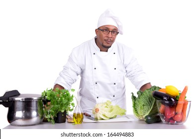 Male chef with fruits and vegetables on table, isolated on white background