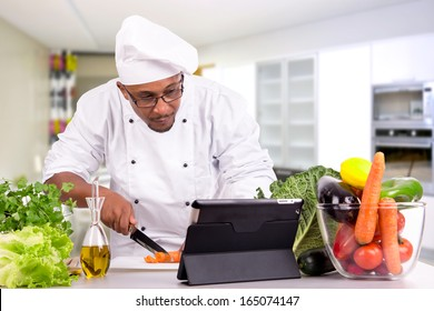Male chef with fruits and vegetables and tablet for recipe