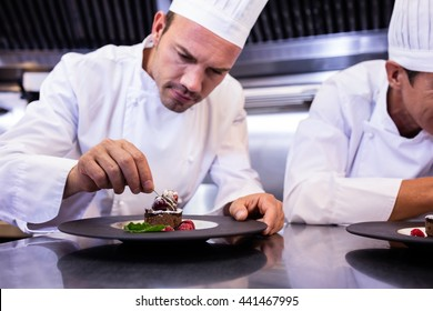 Male chef garnishing dessert plate in commercial kitchen