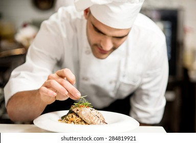 Male chef garnishing his dish, ready to serve