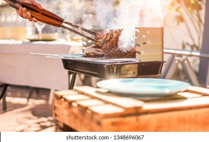 Male chef grill t-bone steak at barbecue dinner outdoor - Man cooking meat for a family bbq meal outside in backyard garden - Summe lifestyle, food and sunday time concept - Focus on hand tongs