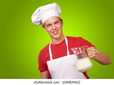 male chef holding jar of milk isolated on red background