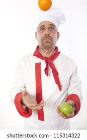 Male chef juggling fruit