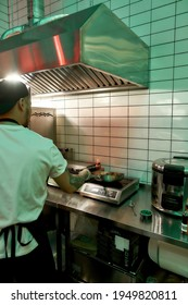 Male chef is making flambe with pan and fire while cooking pork of beef in wok pan, working in commercial kitchen. Asian cuisine concept. Vertical shot