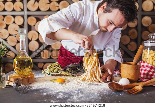 Male chef making homemade pasta with flour and eggs over old wooden table
