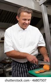 Male Chef Preparing Vegetables In Restaurant Kitchen