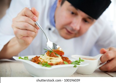 Male chef in restaurant kitchen is garnishing and preparing pasta dish