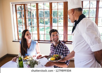 Male chef serving food to young couple sitting in a restaurant