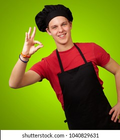 male chef showing ok hand sign isolated on green background