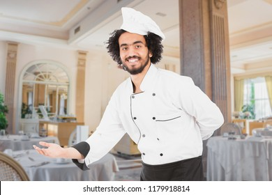 Male chef in a uniform welcoming the guest by hand, standing in a hotel restaurant