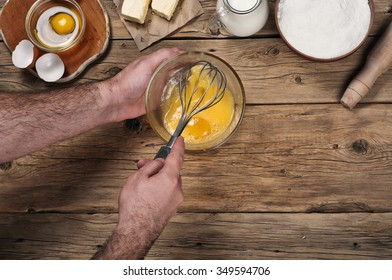 Male chef whipping eggs in the bakery on wooden table. Ingredients for cooking flour products or dough  (flour, eggs, milk, butter). Top view with copy space