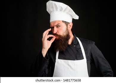 Male chef in white uniform with perfect sign. Professional chef man showing sign for delicious. Serious satisfied bearded chef, cook or baker gesturing excellent. Cook with taste approval gesture.