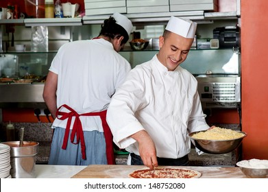 Male chefs working in kitchen, back-office shot