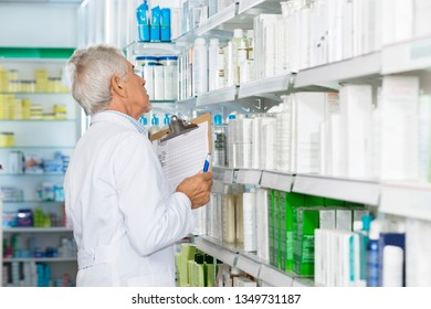 Male Chemist Counting Stock In Pharmacy