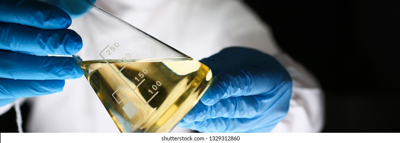 Male chemist hold test tube with yellow liquid biological research closeup. Conducts study urine materials content harmful substances microorganisms human heretical cloning concept