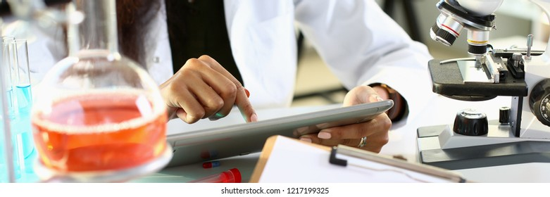 Male chemist holds test tube of glass in his hand overflows liquid solution potassium permanganate conducts analysis reaction takes various versions of reagents using chemical manufacturing water.