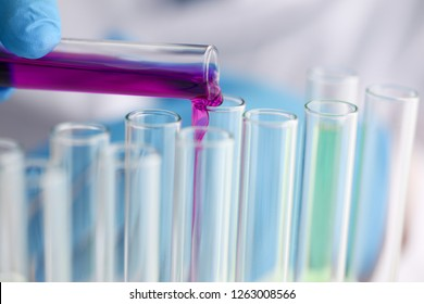 Male chemist holds test tube of glass in his hand overflows a liquid solution of potassium permanganate conducts an analysis reaction takes various versions of reagents using chemical manufacturing.