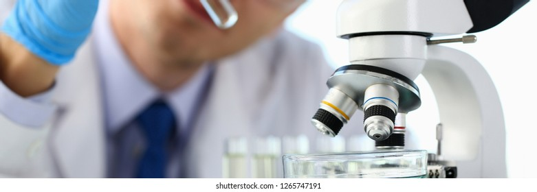 Male chemist holds test tube of glass in hand portrait overflows liquid solution potassium permanganate conducts an analysis reaction takes various versions of reagents using chemical manufacturing.