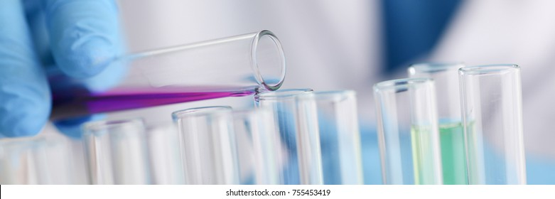 A male chemist holds test tube of glass in his hand overflows a liquid solution of potassium permanganate conducts an analysis reaction takes various versions of reagents using chemical manufacturing.
