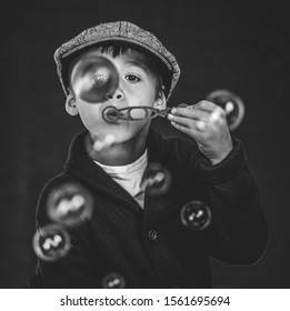 Male child blowing bubbles rendered in black and white.
