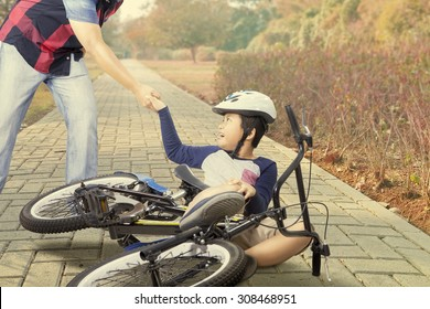 Male child crying after crashing with his bike and helped by his dad on the road