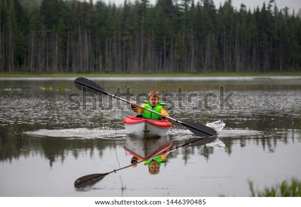 Male child kayaking on a rural lake with  his reflection in the water.
