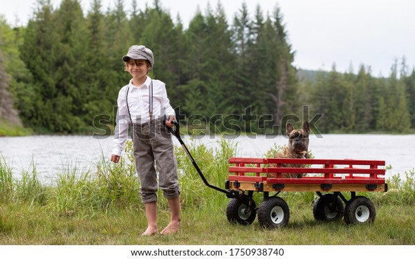 Male child pulling his French Bulldog puppy in a red wagon by the lake.