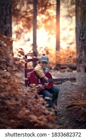 Male child sitting on a red chair in the forest holding a red guitar in his lap.