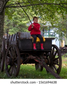 Male child sitting on a retro wooden wagon holding a stick.