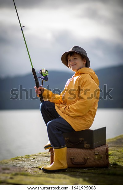 Male child sitting on a wooden dock wearing a yellow rain jacket and boots holding a green fishing rod.