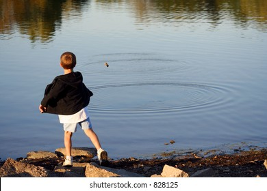 Male Child Skipping Stones on Water – A young boy skipping stones on the water.