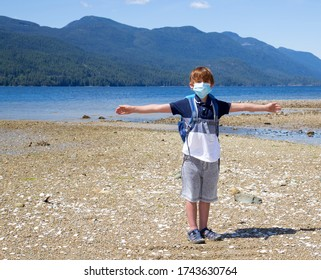 Male child standing at a beach park wearing a mask demonstrating physical distancing.