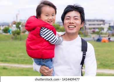 Male childcare, young Japanese family playing in the park