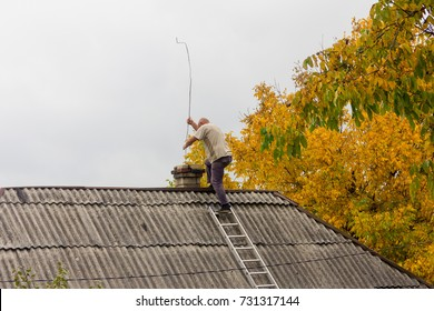 male chimney sweep cleans the chimney on the roof of a village house, the preparation for the heating season