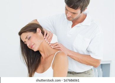 Male chiropractor massaging a young woman's neck in the medical office