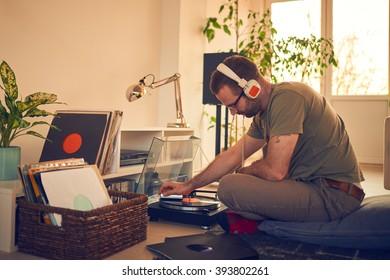 Male choosing next vinyl record to play. Retro gramophone. Audiophile.