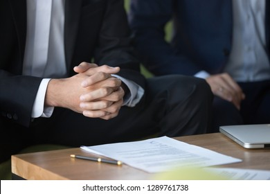 Male clasped hands clenched together, businessman at meeting negotiations or legal advice focused on listening or making decision, consulting about contract, consideration concept, close up view