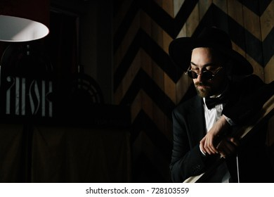 male classical portrait in black on a black background, cowboy