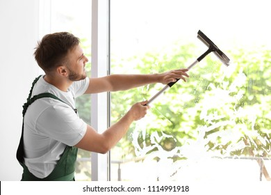 Male cleaner wiping window glass with squeegee indoors