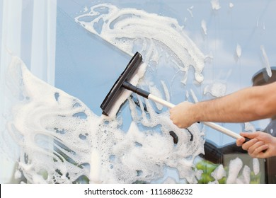 Male cleaner wiping window glass with squeegee from outside, closeup