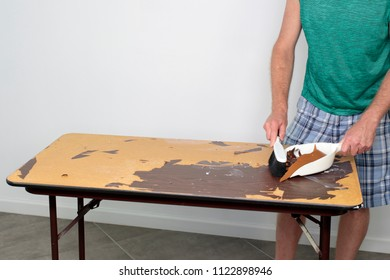 Male cleans off table he is preparing to resurface Male sweeping off a table with a dustpan and broom Guy cleaning old table top surface with dustpan and broom of garbage from preparing to resurface.