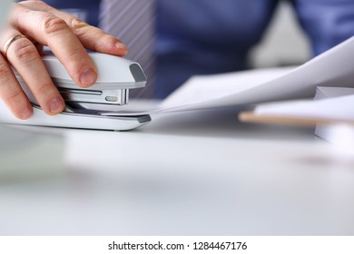 Male clerk arm pin together some papers with stapler closeup. Handy payroll fastener bookkeeper sheet organization concept