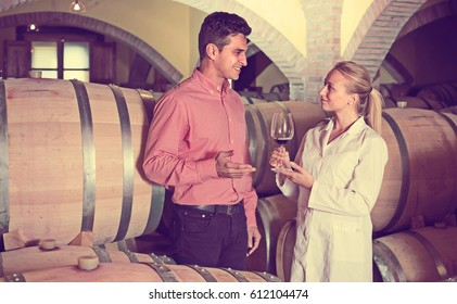 Male client discussing wine from wooden barrels with factory staff